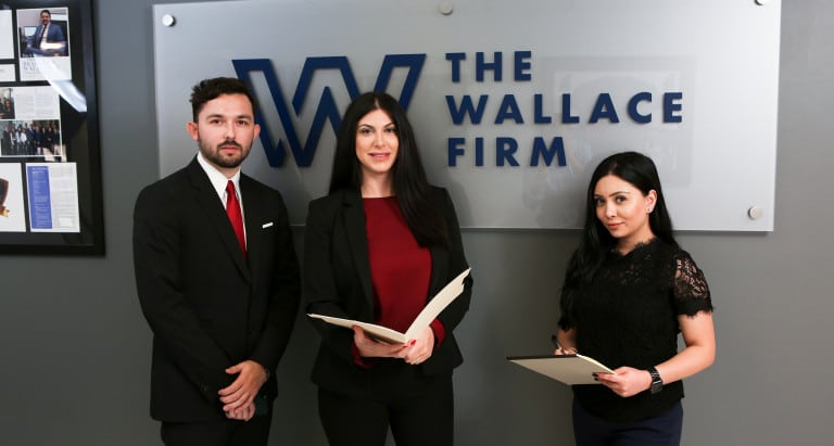 Three employees standing in front of The Wallace Firm logo
